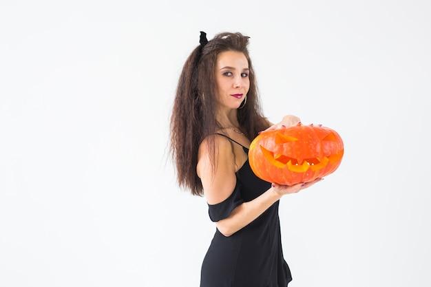 Nette gotische frau in halloween-artkleidung mit kürbis in den händen über heller wand mit kopienraum