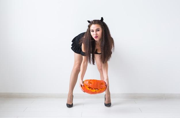 Nette gotische frau in halloween-stilkleidung mit kürbis in den händen über hellem hintergrund mit kopienraum