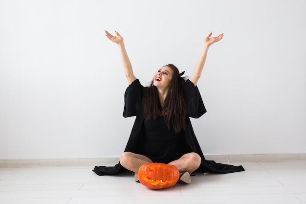 Nette gotische frau in halloweenartkleidung mit kürbis in den händen