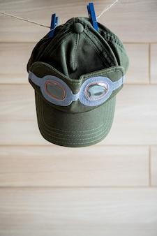 Nette grüne kappe hängen an der wäscheleine und an der hölzernen hintergrundwand
