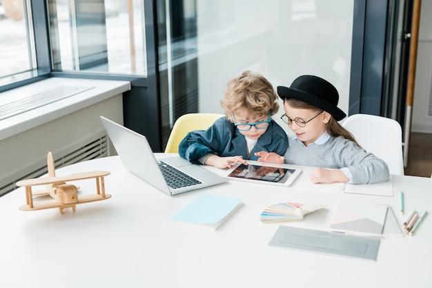Nette grundschulfreunde mit digitalem tablett, das durch online-informationen im klassenzimmer im unterricht scrollt