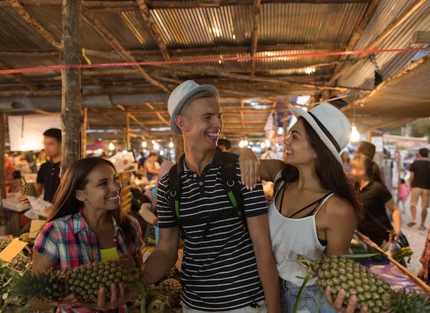 Nette gruppe freunde kaufen ananas auf tropischem straßenmarkt in der jungen touristen-holding thailands