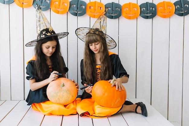 Nette halloween-hexen, die auf kürbise zeichnen