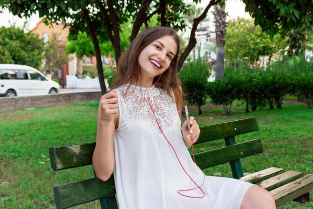 Nette herrliche frau hört musik in den kopfhörern und tanzt auf die bank in den park an einem warmen tag