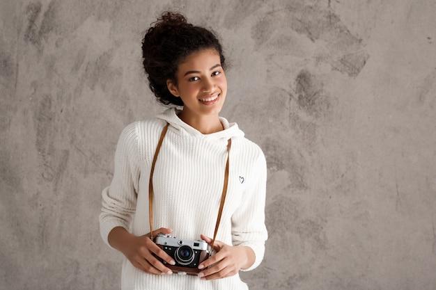 Nette hipsterfrau, die fotos auf retro-kamera macht