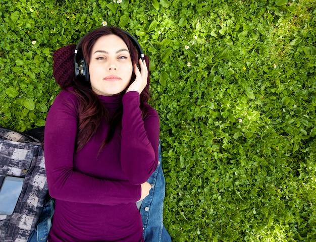 Nette hörende musik der jungen frau mit kopfhörern
