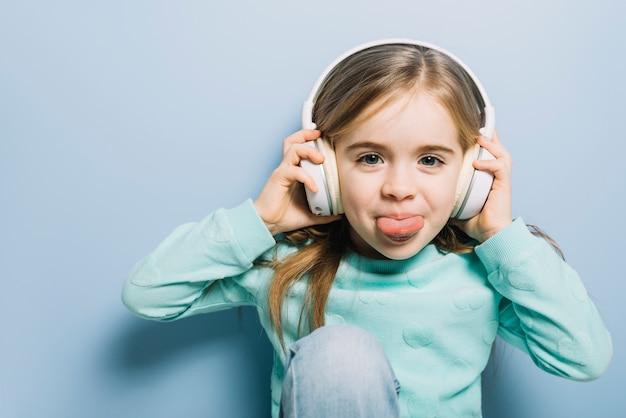 Nette hörende musik des kleinen mädchens auf dem kopfhörer, der heraus ihre zunge haftet