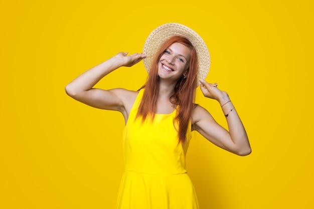 Nette ingwerfrau lächelt in die kamera auf einer gelben studiowand und hält ihren schönen hut