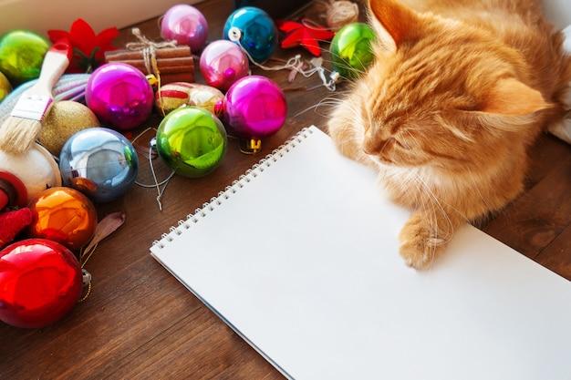 Nette ingwerkatze, die auf klarer papierseite unter weihnachtsdekorationen liegt
