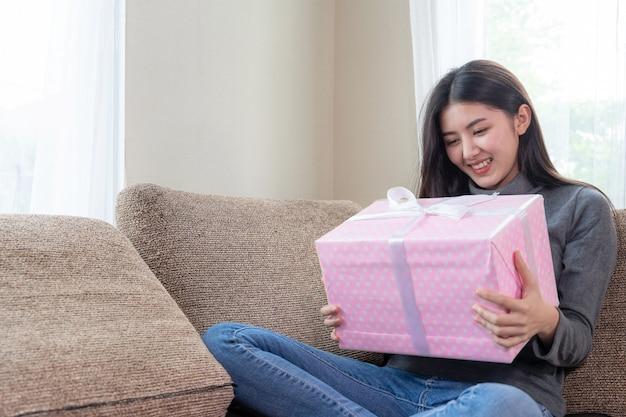 Nette jugendfrau, die glücklich sich fühlt und die rosa geschenkbox anwesend auf couch umarmt
