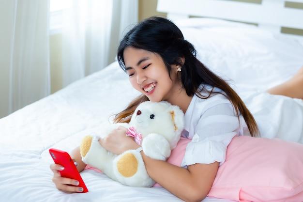 Nette jugendfrau froh mit smartphone auf bett