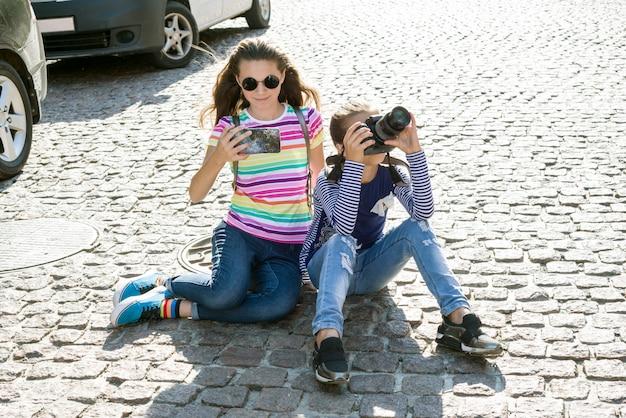 Nette jugendlich mädchen benutzen kamera und smartphone für foto
