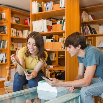 Nette jugendliche, die tablette in der bibliothek betrachten