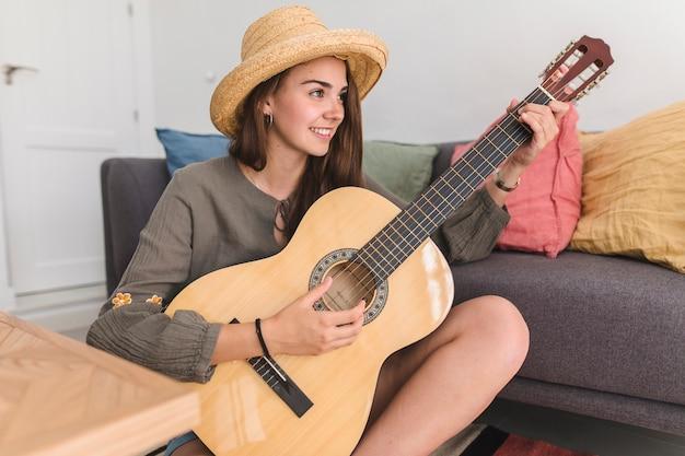 Nette jugendliche, die zu hause gitarre spielt