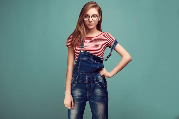 Nette jugendliche im denimoverall und -gläsern