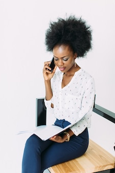 Nette junge afroamerikanische geschäftsfrau, die am handy, sitzend auf dem stuhl, lokalisiert auf weiß spricht