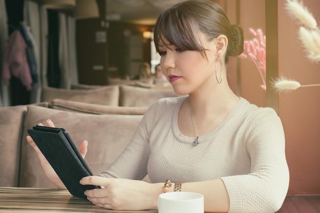 Nette junge asiatische frau, die in einem café sitzt, hält ein tablet in der hand und schaut auf einen bildschirm