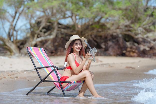 Nette junge asiatische frau im bikini am schönen strand in den sommerferien in thailand