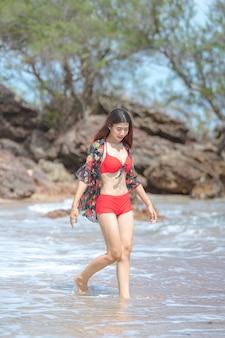 Nette junge asiatische frau im bikini glücklich am schönen strand in den sommerferien in thailand