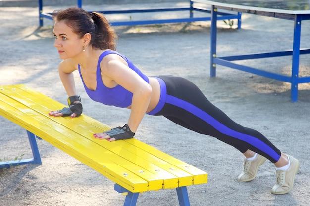 Nette junge athletische frau, die gymnastik auf ihren händen tut