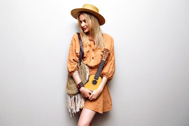 Nette junge blonde frau, die ukulele mit boho modischem kleid und strohhut hält