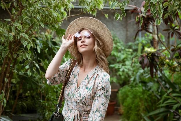 Nette junge blonde frau, die unter dem grün im gewächshaus aufwirft und lächelt