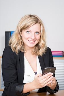 Nette junge blondine, die intelligentes telefon halten und es mit lächeln beim sitzen neben arbeitsplatz betrachten