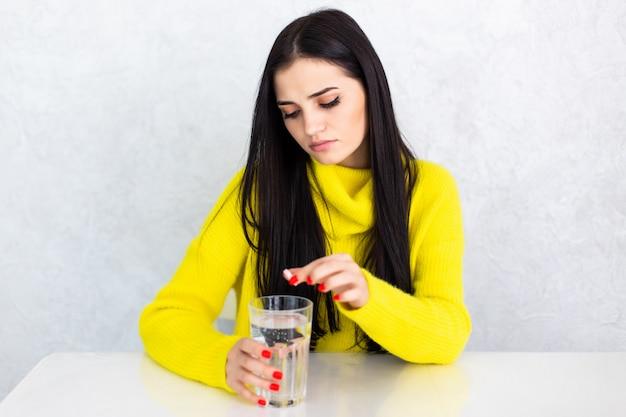 Nette junge brünette frau, die eine pille mit einem glas wasser zu hause nimmt