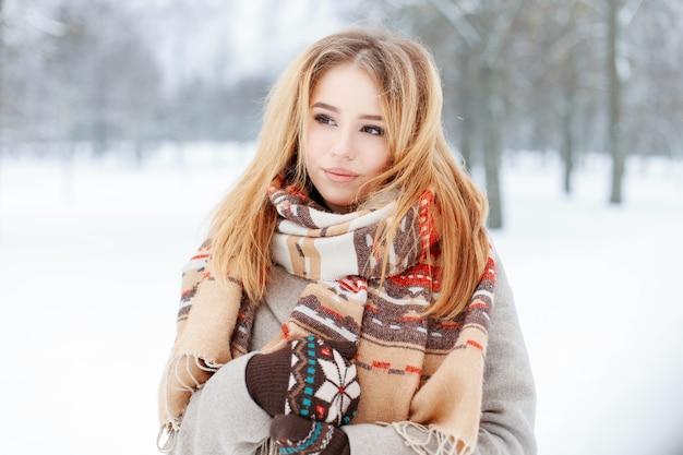 Nette junge charmante zarte frau mit stilvollem vintage-schal im trendigen warmen grauen mantel mit gestrickten fäustlingen