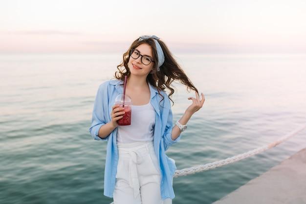 Nette junge dame im weißen kleid und in der blauen strickjacke, die spielerisch auf ozeankai aufwirft und am morgen soda trinkt