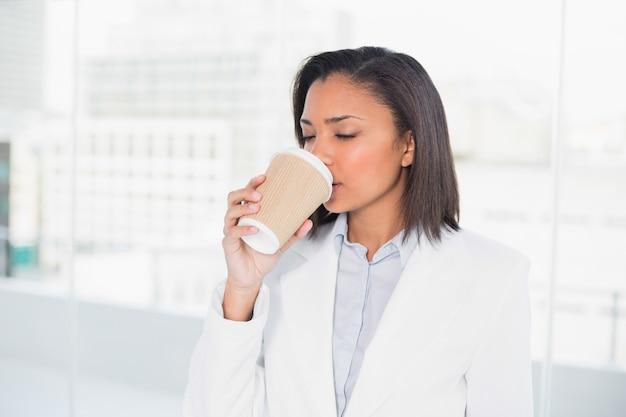 Nette junge dunkelhaarige geschäftsfrau, die kaffee genießt