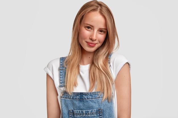 Nette junge europäische frau mit hellem haar, gekleidet in lässigem weißem t-shirt und jeans-latzhose, hat zufriedenen ausdruck, isoliert über weißer wand. menschen-, schönheits- und lifestyle-konzept.