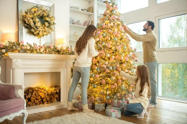 Nette junge familie, die weihnachtsbaum zu hause verziert