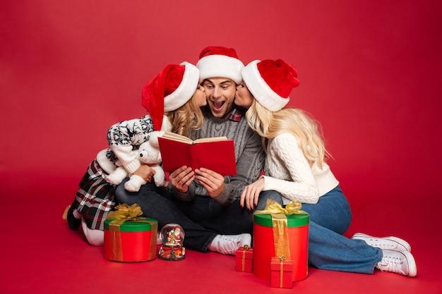 Nette junge familie, die weihnachtshüte trägt
