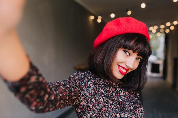 Nette junge französin in stilvoller kleidung posiert, lächelt verlegen und winkt mit der hand. porträt des entzückenden brünetten mädchens im trendigen roten hut und im retro-kleid, die spaß drinnen auf unschärfehintergrund haben