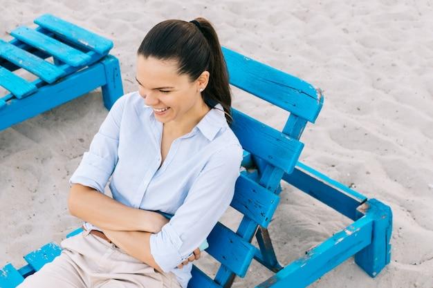 Nette junge frau, die auf einer bank auf dem strand und dem lachen sitzt