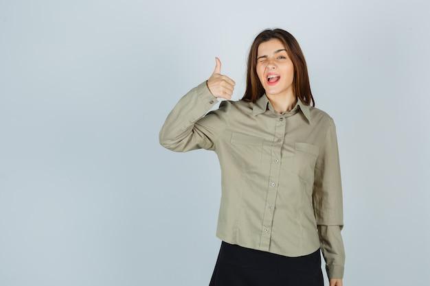 Nette junge frau, die daumen zeigt, während sie in hemd, rock blinkt und stolz aussieht, vorderansicht.