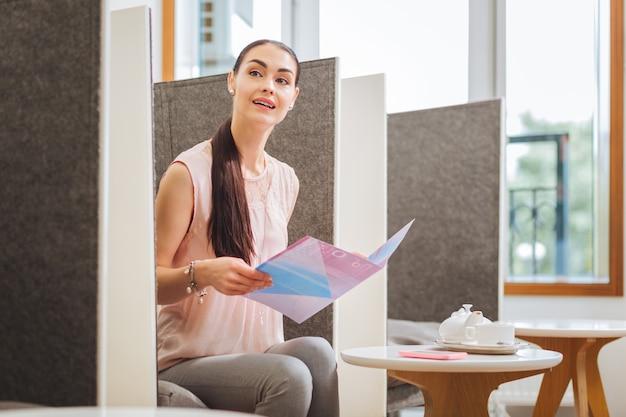 Nette junge frau, die eine zeitschrift liest, während sie auf einen termin mit einer kosmetikerin wartet