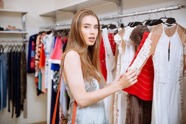 Nette junge frau, die einkaufen und kleid im bekleidungsgeschäft wählt