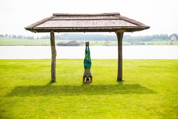Nette junge frau, die handstandübungen im grünen park tut