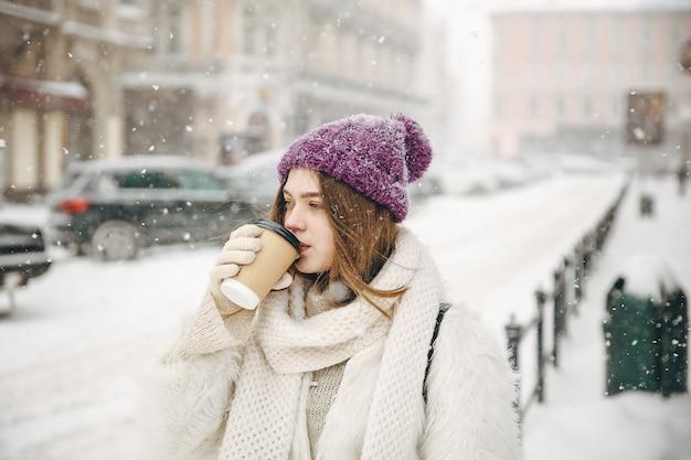Nette junge frau, die heißen frischen kaffee vom wegwerfbecher trinkt, während draußen während des schneefalls steht.