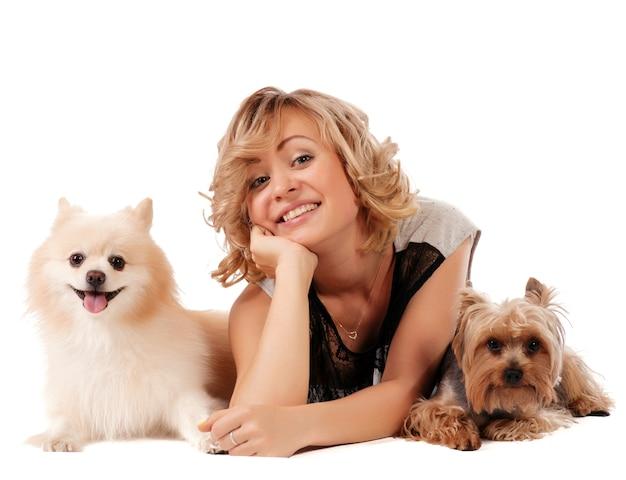 Nette junge frau, die ihre hunde beim sitzen lokalisiert auf weiß - portrait streichelt