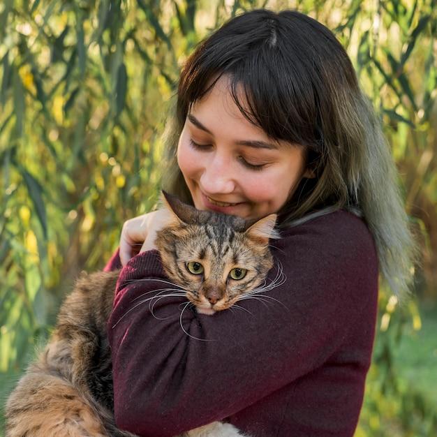 Nette junge frau, die ihre katze der getigerten katze im garten liebt