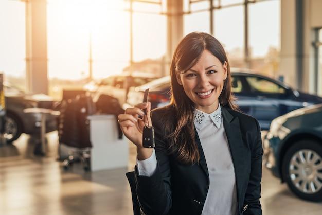 Nette junge frau, die ihren neuwagenschlüssel an der verkaufsstelle zeigt.