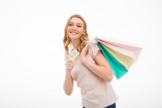 Nette junge frau, die kreditkarte und einkaufstaschen hält.