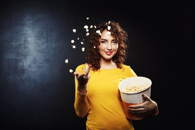 Nette junge frau, die lächelnd popcorn in die luft wirft