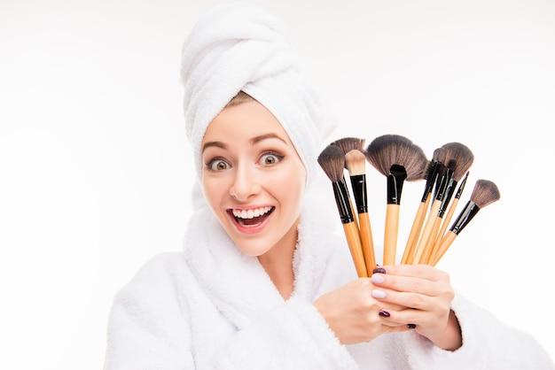 Nette junge frau, die make-up-bürsten mit handtuch auf ihrem kopf hält