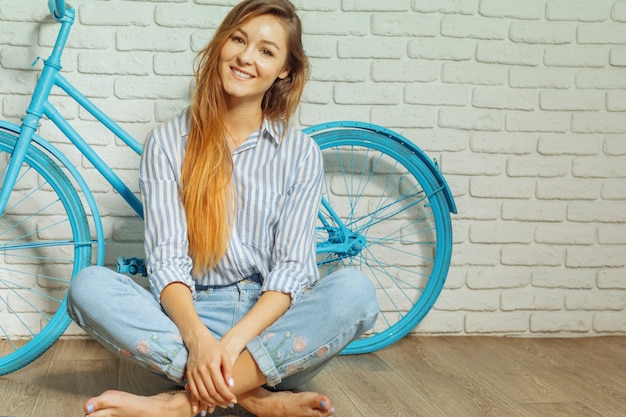Nette junge frau, die nahes fahrrad steht