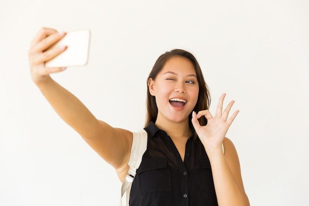 Nette junge frau, die selfie mit smartphone nimmt