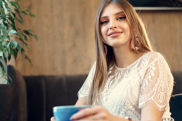Nette junge frau, die tasse kaffee in einer kaffeestube genießt
